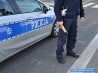 Policjant na tle radiowozu