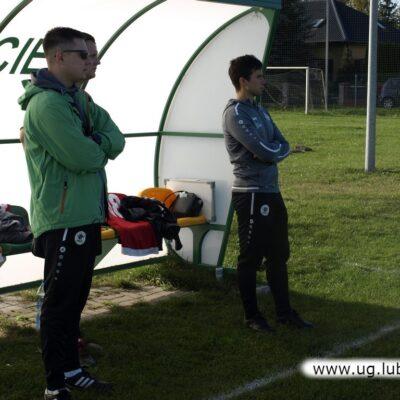 Ławka gości, trener obserwuje boisko.