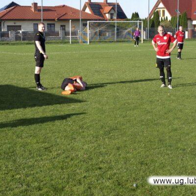 Kontuzjowany piłkarz z Obory, nad nim sędzia.