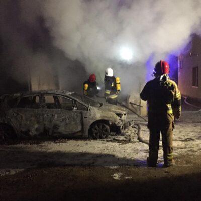Tumany dymu, wrak auta i strażacy dogaszający pożar.