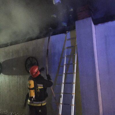 Strażacy w aparatach ochrony dróg oddechowych, jeden na dachu garażu.
