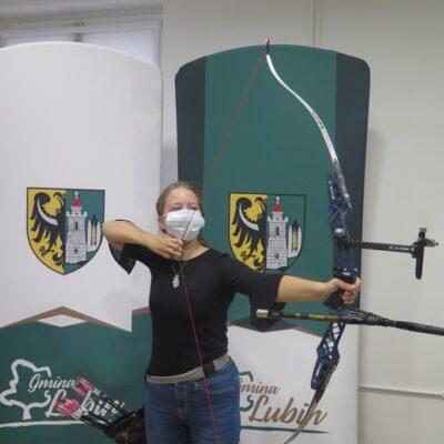 Magdalena Sieradzka z łukiem, strzałami, na tle herbu Gminy Lubin.