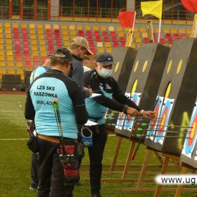 Zawodnicy i sędziowie przy tarczach strzelniczych.