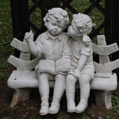 Ogrodowa figurka chłopiec i dziewczynka na ławce.
