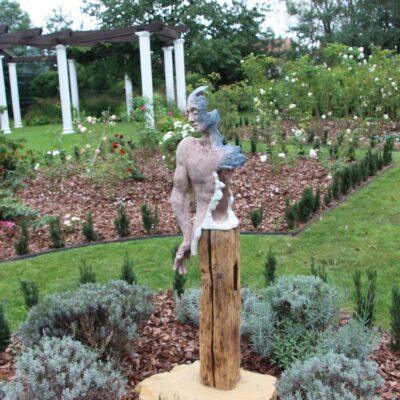 Gliniana figura na tle części różanej ogrodu.
