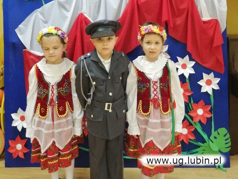Dziewczynki w ludowych strojach i chłopiec w mundurze.
