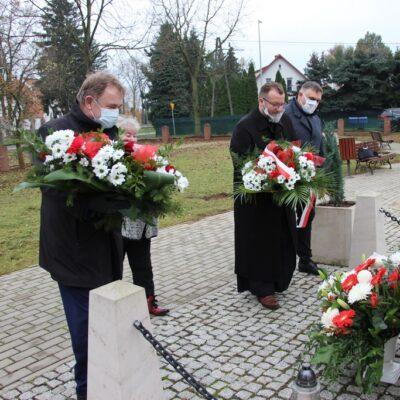 Wójt Tadeusz Kielan, proboszcz Paweł Kajl, sołtys Alina Majewska i przewodniczący Rady Gminy Norbert Grabowski składają kwiaty pod tablicą pamięci Józefa Piłsudskiego.