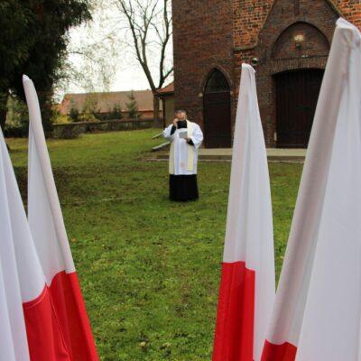 Kisądz Tadeusz Żurek na tle flag