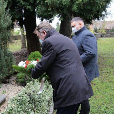 Wójt i przewodniczący składają kwiaty.