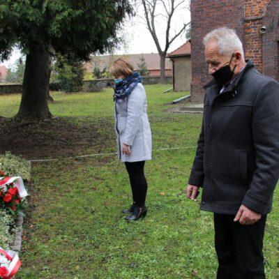 Sołtys Stanisław Ryniec i Agnieszka Szumlańska składają kwiaty.