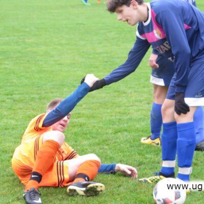 Piłkarz z Raszówki pomaga wstać po faulu na zawodniku Kryształu.