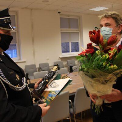 Wójt wręcza kwiaty Łukaszowi Kurkowi.