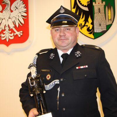 Łukasz Kurek trzyma statuetkę strażaka roku.