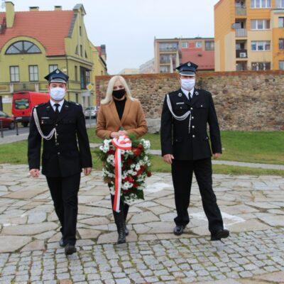 Delegcja Gminy Lubin z wiązanką idzie w keirunku pomnika.