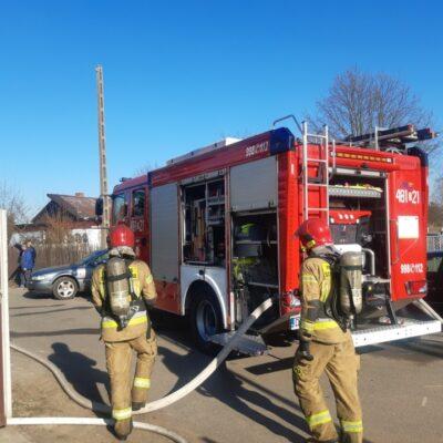 Strażacy na tle wozu gaśnieczego.