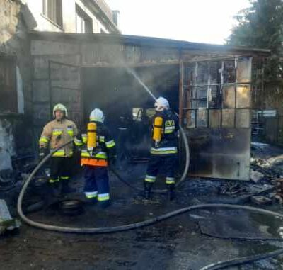 Strażacu z wężąmi gaszą pożar.