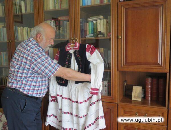 Stanisław Jaszowski z dumą prezentuje strój z przełomu XIX i XX wieku, który jego babcia Katarzyna zakładała na ważne uroczystości