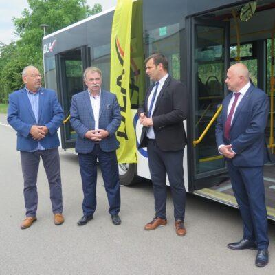Wójt, burmistrz oraz przedstawiciele przeoźnika na tle autobusu.