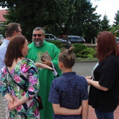Ksiądz Artur przed kościołem z wiernymi.