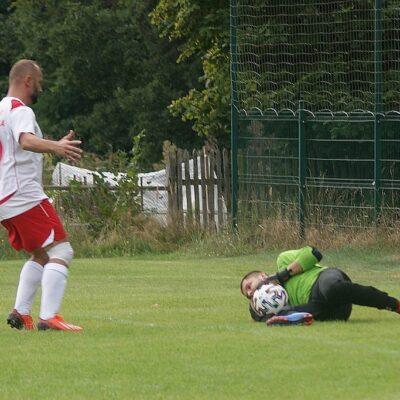 Bramkarz łapie piłkę.